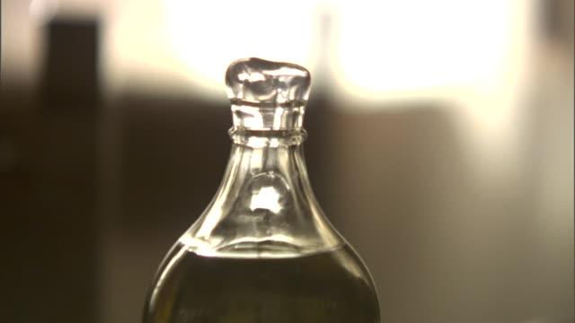 vídeos de stock e filmes b-roll de a hand pours oil from a carafe onto a garden salad. - tempero