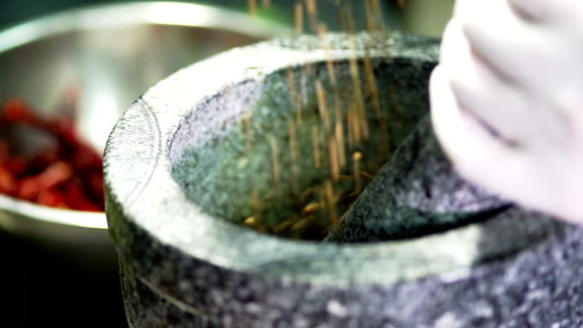 hand pours spices and herb ingredient into the mortar. - pietra materiale da costruzione video stock e b–roll