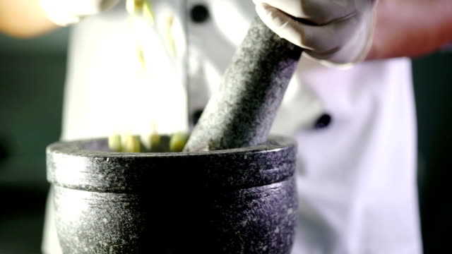 Hand pours spices and herb ingredient into the mortar.