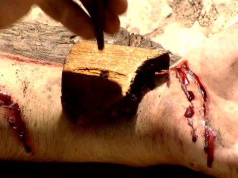 a hand prepares to nail jesus' arm to the cross. - jesus christus stock-videos und b-roll-filmmaterial