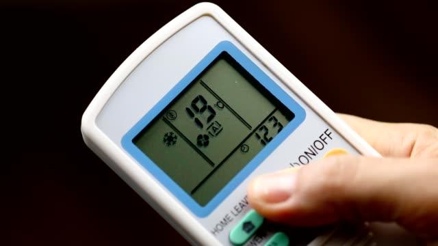 handdrücken an der fernbedienung, um die raumtemperatur zu erhöhen - temperatur stock-videos und b-roll-filmmaterial