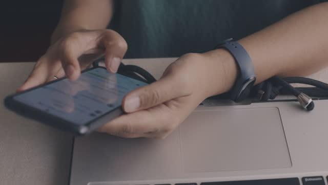 vídeos de stock e filmes b-roll de hand pressing phone with laptop on background. - e mail