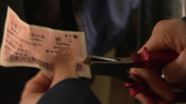 A hand punches tickets with a hole punch.
