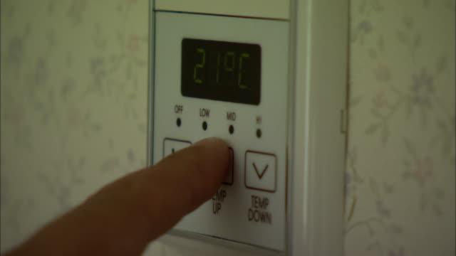 vidéos et rushes de cu hand pushing buttons of thermostat, shanghai, china - température