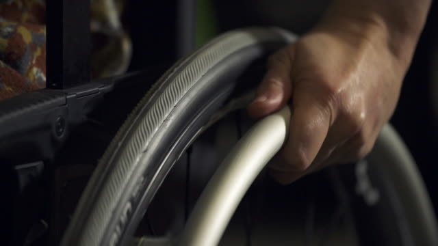 Hand pushing wheelchair forward
