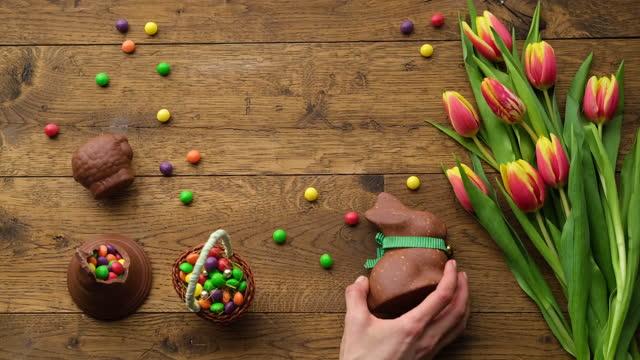 eine hand legt ein schokoladenkaninchen auf den holztisch. - blütenblatt stock-videos und b-roll-filmmaterial