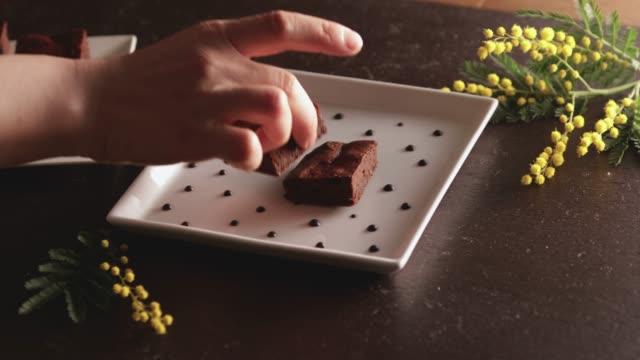 Eine Hand legt eine Torschokolade auf einen Teller.