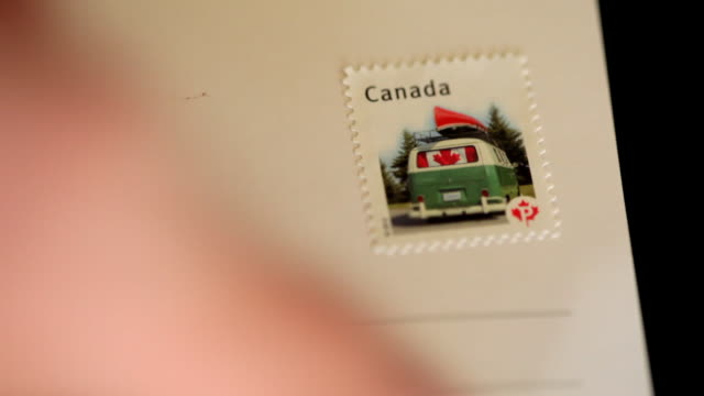 CU of hand putting Canadian stamp on postcard