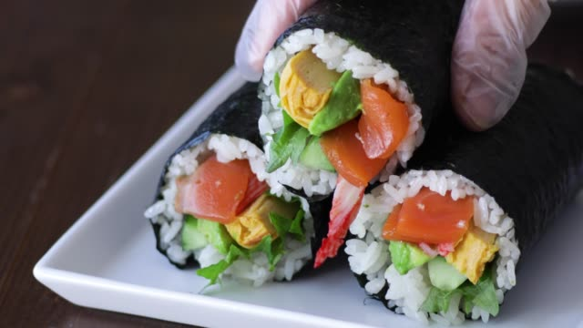 hand putting sushi rolls on a plate. - shiso stock videos & royalty-free footage