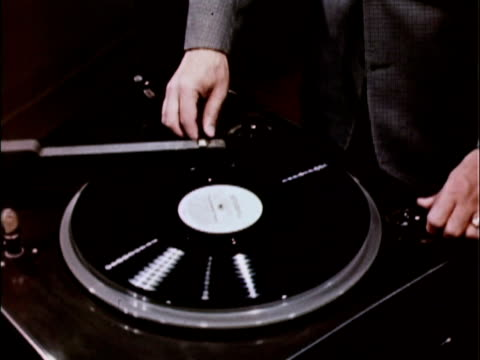 1956 cu hand putting tone arm onto record on radio transcription turntable / usa - putting stock videos and b-roll footage