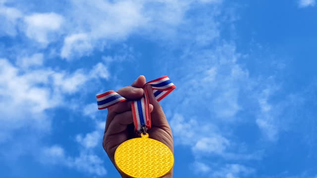 hand raised, holding gold medal against sky. award and victory concept - gold medalist stock videos & royalty-free footage