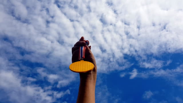hand raised, holding gold medal against sky. award and victory concept