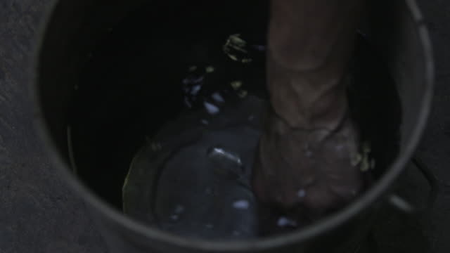 a hand reaches into a bucket and pulls out a glass 'prince rupert's drop', uk. - prince stock videos and b-roll footage