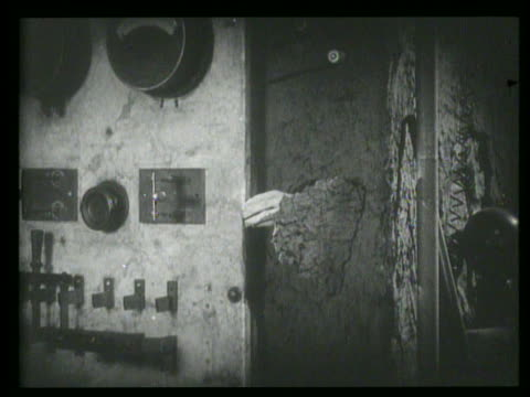 b/w hand reaches through wall + pulls lever in laboratory - 無声映画点の映像素材/bロール