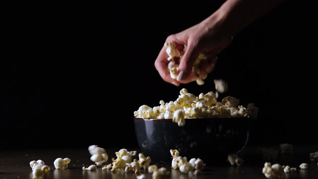 hand reaching for popcorn on black background. - obsessive stock videos & royalty-free footage
