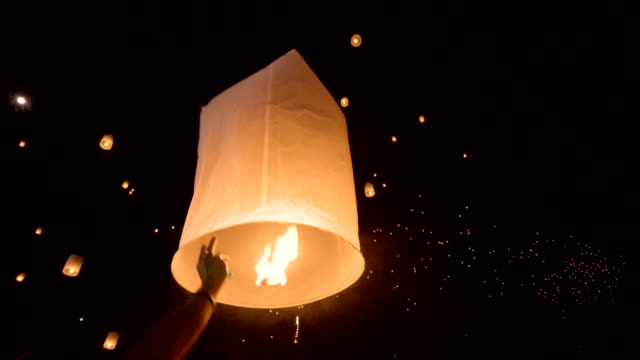 vídeos de stock e filmes b-roll de hand releasing hot air paper lantern up to the sky in yi peng festival, chiang mai, thailand. - levantar