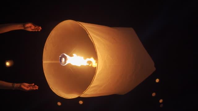 vídeos de stock e filmes b-roll de slo mo hand releasing lantern to the sky in yee peng festival (yi peng) - lanterna de papel