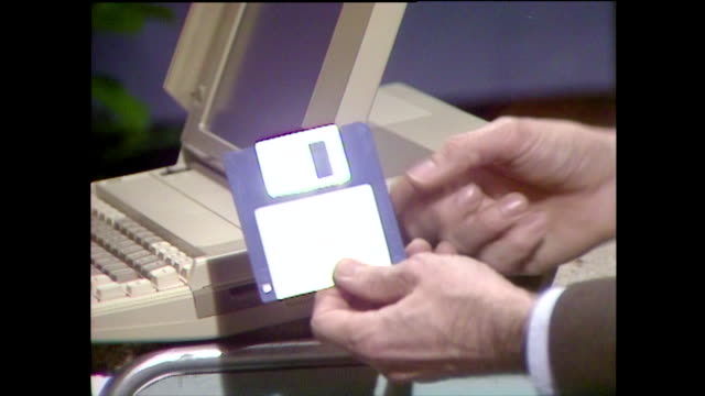 "vídeos de stock e filmes b-roll de hand removes 3.5"" floppy disk from drive on laptop; 1985 - 1985"