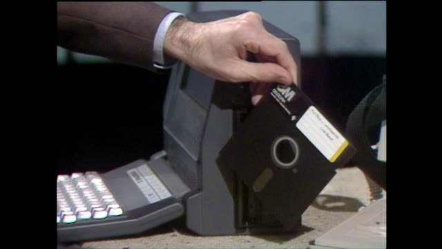 vídeos de stock e filmes b-roll de hand removes large floppy disk from drive on laptop; 1985 - 1985