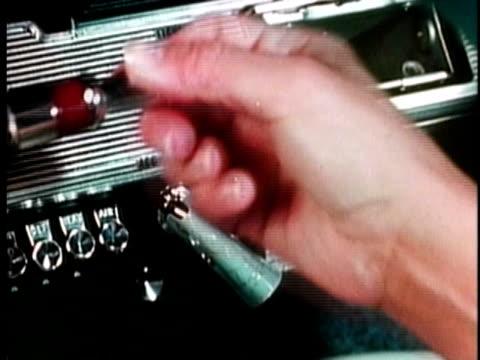 1961 CU Hand removing cigarette lighter in car / United States / AUDIO