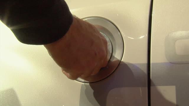 cu zi hand removing cover to charging port for hybrid vehicle/ detroit, michigan - 部分点の映像素材/bロール