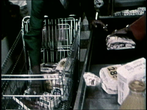 hand removing groceries from shopping cart and putting them on conveyor belt at cash register - 1972 stock videos and b-roll footage