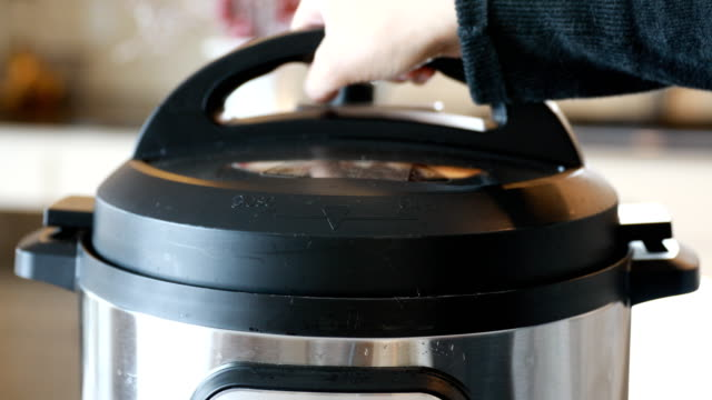 hand removing pressure cooker lid - utensil stock videos & royalty-free footage