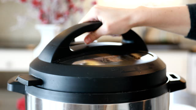 hand removing pressure cooker lid with steam - cooking pan stock videos & royalty-free footage