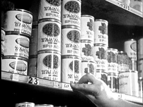 1945 b/w montage cu hand removing price tag on shelf stacked with canned spinach and corn / audio - price tag stock videos & royalty-free footage