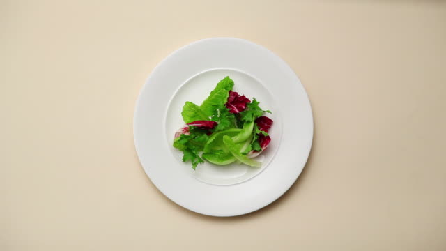 CU Hand removing vegetable salad from white backdrop / Seoul, South Korea