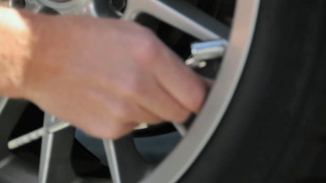 cu hand replacing valve cap on tire, california, usa - 空気弁点の映像素材/bロール
