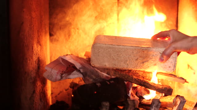CU of hand restarting fire in fireplace and adding eco friendly log