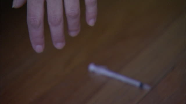 a hand rests next to a used hypodermic needle. - injecting heroin stock videos & royalty-free footage