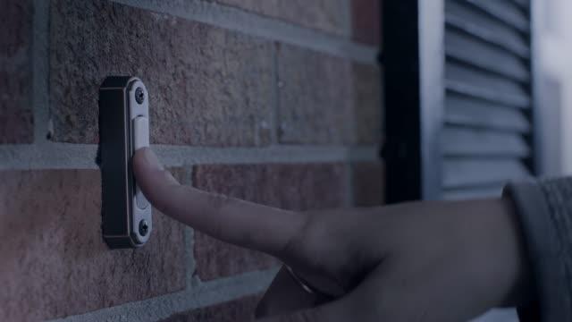 stockvideo's en b-roll-footage met cu. hand rings doorbell outside brick house at night. - aanbellen