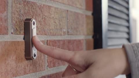 vídeos y material grabado en eventos de stock de cu. hand rings doorbell outside brick house on sunny day. - ladrillo