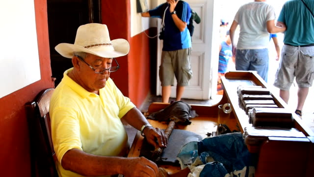 Hand rolling custom Cuban cigars. Man making cigars in La Canchanchara a tourist landmark in Trinidad,Cuba