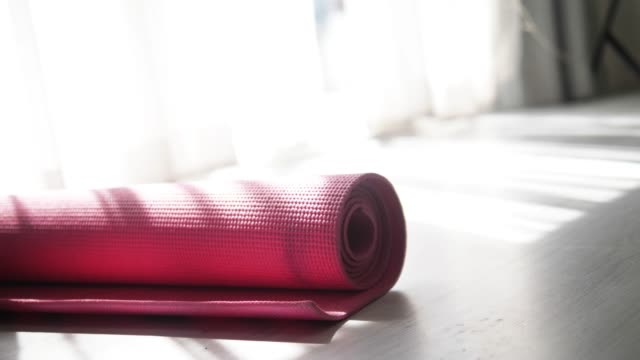 hand rolling pink yoga mat on the floor at home, lifestyle concept. - rolling stock videos & royalty-free footage