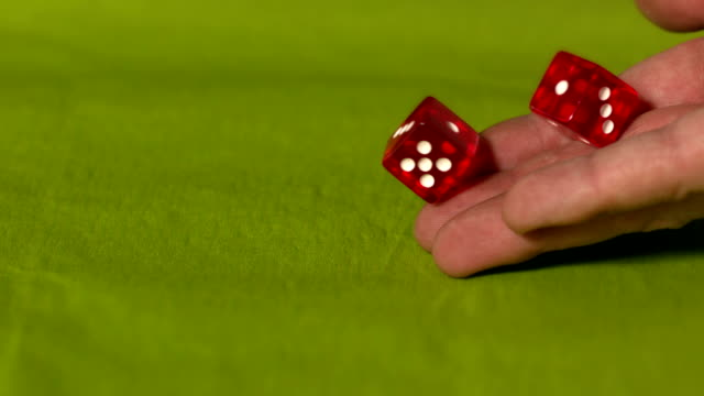 Hand rolling two red dice on green table
