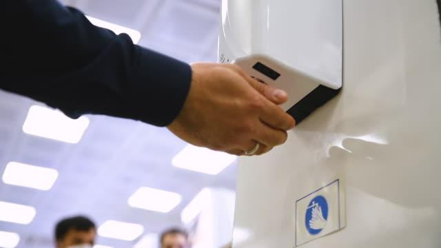 vídeos de stock e filmes b-roll de hand sanitizer in market. people sanitize their hands before shoppin - higiene