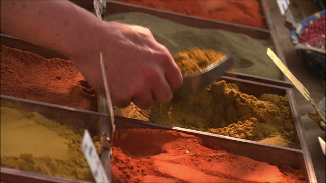 cu tu hand scooping spice and putting into plastic cover at market stall / arles, provence, france - gewürz stock-videos und b-roll-filmmaterial