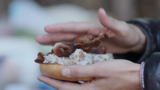 ecu. hand scoops potato hash and bacon on toasted bagel for campfire breakfast. - サンドイッチ作り点の映像素材/bロール