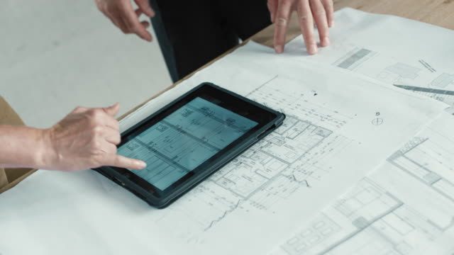 hand scrolling the construction plans on the digital tablet set on the table on top of plan sheets - two people stock videos & royalty-free footage