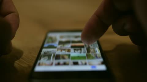 cu-hand blättern durch fotos auf smartphone - image stock-videos und b-roll-filmmaterial