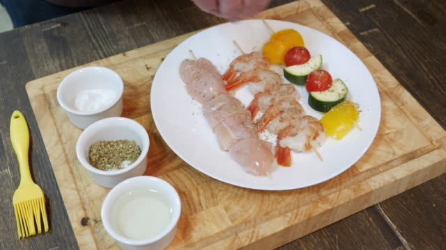 hand seasoning seafood meat and vegetables on skewers - courgette stock videos and b-roll footage