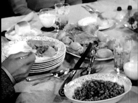1945 b/w cu hand serving dish onto plate and placing it to guest at table / united states / audio - 1945 stock videos & royalty-free footage