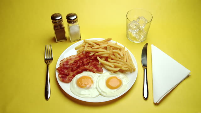 CU Hand serving Fried eggs, bacon and Chips with cold drink