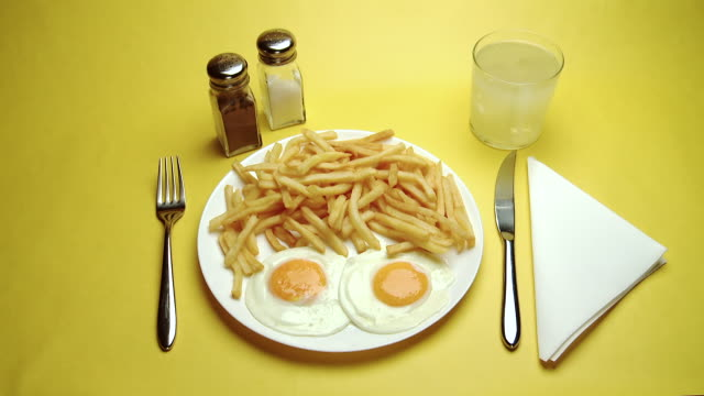 cu hand serving fried eggs & chips - yellow background stock videos & royalty-free footage