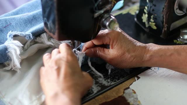 vídeos de stock, filmes e b-roll de mão sewn para reparar as calças de brim com máquina velha. - material têxtil