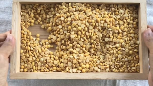 hand shaking and smoothing soybeans in wooden tray - dried food stock videos & royalty-free footage