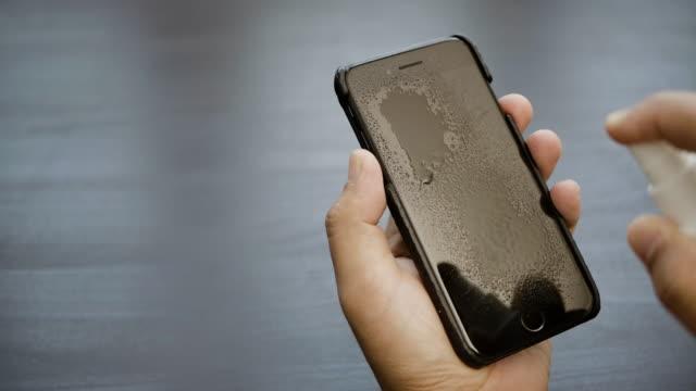 hand skott av en man ren desinficera sin smarta telefon med alkohol desinfektionsmedel spray - människofinger bildbanksvideor och videomaterial från bakom kulisserna